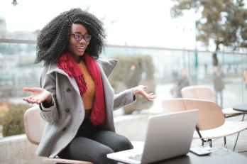cheerful surprised woman sitting with laptop